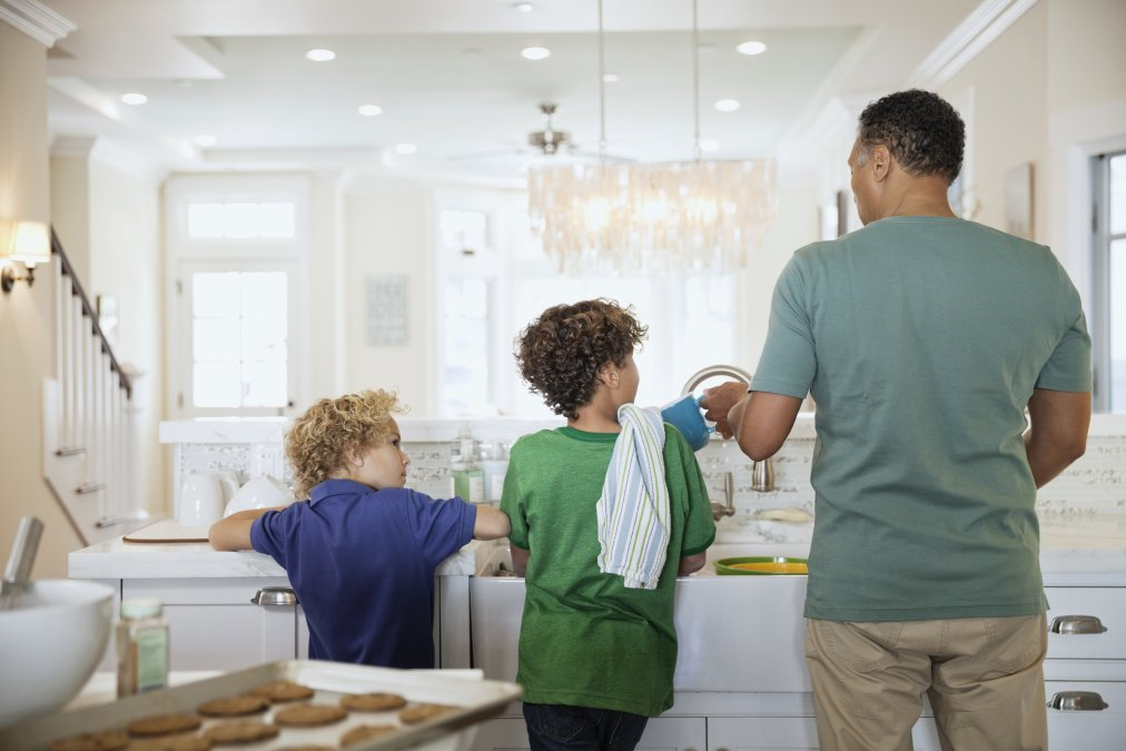 Rear view of children and father washing dishes at kitchen sink